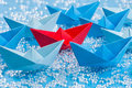 Fleet of blue origami paper ships on blue water like background surrounding a red one waterlike in the middle Royalty Free Stock Photo