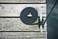 Flemish coil on weathered dock black boat line secured cleat and arranged sun bleached grey boards in Royalty Free Stock Images