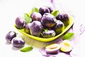 Fleshy plums in a bowl on the table Royalty Free Stock Photo
