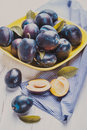 The fleshy plums in a bowl on table Royalty Free Stock Photography