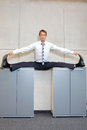 Flexible business man in the center split position on cabinets fit or straddle Royalty Free Stock Photo