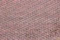 Flexible shingles of red-brown color on the house roof. Royalty Free Stock Photo