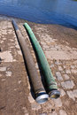 Flexible tubes for disposing liquid manure in the river two Royalty Free Stock Photos
