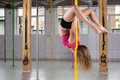 Flexible woman doing pole dance young in fitness club Royalty Free Stock Photo