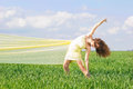 Flexible young woman in a green field Stock Images