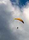 Flight above the clouds yellow parachute flying in front of huge Stock Image