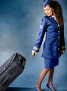 Flight attendant dragging luggage and smiling Royalty Free Stock Photo