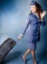 Flight attendant dragging luggage and waving goodbye Royalty Free Stock Photos