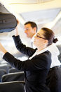 Flight attendant helping passenger Stock Image