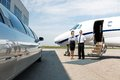 Flight attendant and pilot neat limousine and standing private jet at airport terminal Royalty Free Stock Photo