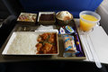In flight meal on gulf air aircraft coach class during commercial from seat chicken rice orange juice and chocolate cheesecake Royalty Free Stock Photography