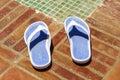 Flip flop slippers beside a pool shower