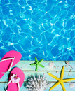 Flip-flop, starfish, seashells and coral on wooden plank and pool Royalty Free Stock Photo