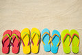 Flip flops on beach four pairs of sandals white sand Royalty Free Stock Images