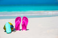 Flip flops, coconut and suncream on white sand. Beach accessories. Royalty Free Stock Photo