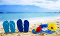 Flip flops and hat with tropical flowers on sandy beach Royalty Free Stock Photo