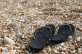 Flip flops a pair of black on a beach Royalty Free Stock Image