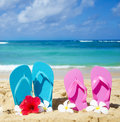 Flip flops on sandy beach with tropical flowers in hawaii kauai Stock Images