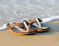 Flip flops on a sandy ocean beach Royalty Free Stock Photos