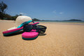 flip flops, straw hat and sunglasses on tropical beach Royalty Free Stock Photo