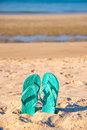 Flip flops stuck in the sand of a beach sea background Royalty Free Stock Image