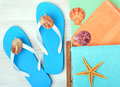 Flip-flops, towel, starfish and seashells. Royalty Free Stock Photo