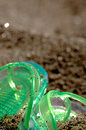 Flipflop in the sand green on a beach covered by Royalty Free Stock Image