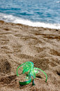 Flipflop in the sand green on a beach covered by and sea background Royalty Free Stock Photos