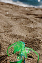 Flipflop and towel in the sand green on a beach covered by sea background Stock Image