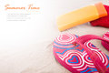 Flipflops sunscreen towel on beach sand Stock Photography