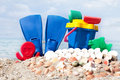 Flipper and child toys on a sandy beach blue seashells Royalty Free Stock Images