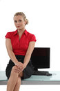Flirtatious secretary sitting on the table Stock Images
