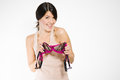 Flirtatious young woman holding a sexy bra beautiful with teasing smile with pink lace in her hands as she looks at the camera Royalty Free Stock Images