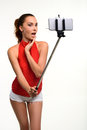 Flirting girl takes picture of herself young woman with monopod on white background student wearing bright clothes making selfie Stock Images