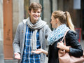Flirting at the street girl in leather jacket with smiling young guy Royalty Free Stock Image