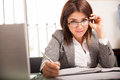 Flirty business woman at work cute latin flirting and playing with her glasses while working in her office Royalty Free Stock Image