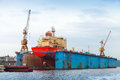 Floating blue dry dock with red tanker under repair inside back view Stock Images