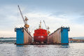 Floating blue dry dock with red tanker under repair inside frontal view Stock Photo