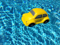 A floating car yellow toy on blue swimming pool Royalty Free Stock Images