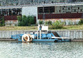 Floating machinery docked harbor in front of dilapidated building Royalty Free Stock Photo