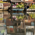 Floating market with reflection in water at Mekong river Royalty Free Stock Photo