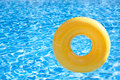 Floating ring on blue water swimpool with waves reflecting in the summer sun Stock Photo