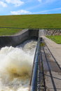 Flood control outlet lake at maximum capacity releasing water at cubic feet a second is located at bottom of a earthen dam Stock Photography