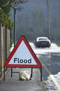 Flood sign motorist driving through waters with warning in foreground Stock Images