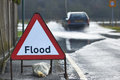 Flood sign motorist driving through waters with warning in foreground Stock Photo