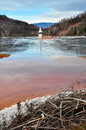 A flooded church in a toxic red lake water polluting by a coppe copper mine rosia montana romania Stock Photo