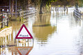 Flooded road and sign warning half submerged Stock Image