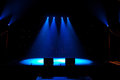 Floodlit stage a dark moody lit by four bue spotlights in the centre Royalty Free Stock Images