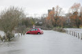 Floods engulf red car a is caught on a country road as a swollen river breaks its banks england uk Royalty Free Stock Photos