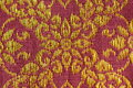 Flora pattern thai silk a beautiful piece of very fine of golden flower liked design on pink and brown background Royalty Free Stock Image